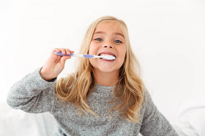 Close-up portrait of cute kid in gray pajamas brushing her teeth, looking at camera
