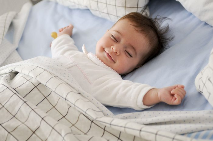 Smiling baby girl lying on a bed sleeping on blue sheets