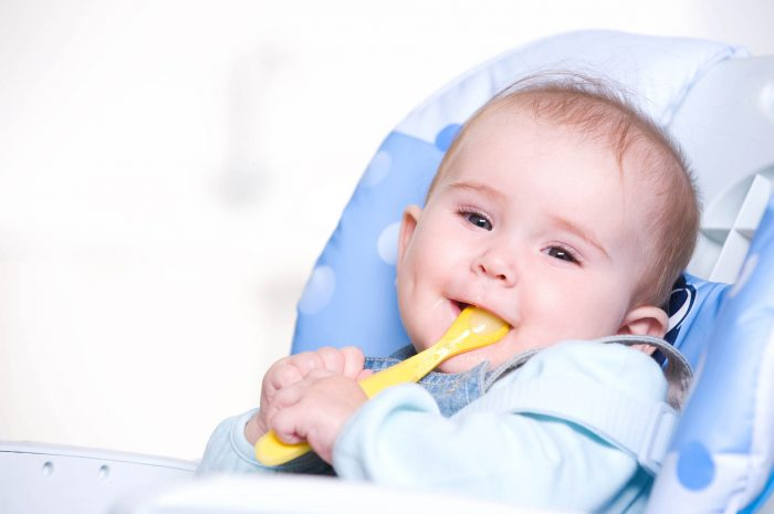 Beautiful happy baby with spoon sitting on highchair