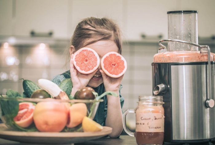 little cute happy girl preparing juice fresh in the kitchen, concept of healthy baby food and happy family